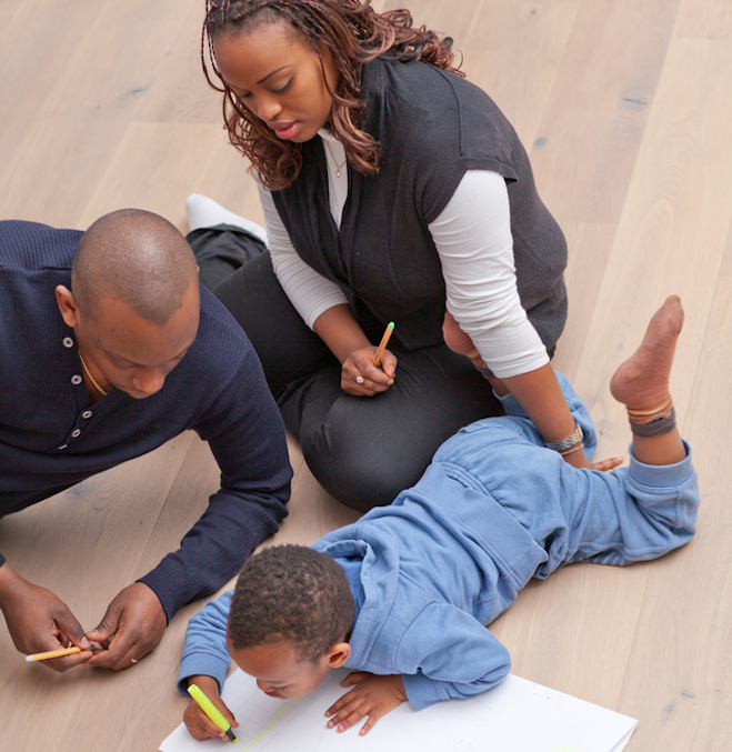 Two adult caregivers on the floor with a young boy coloring with markers