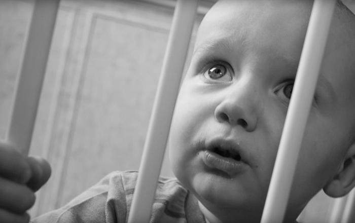 Black and white photo of a worried baby behind crib bars