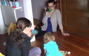 A coach filming a mother and children in a home setting. Photo courtesy of FIND.