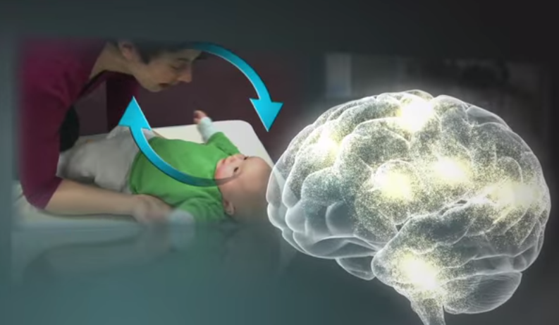 Serve and return video still showing a caregiver interacting with an infant, with a graphic showing a developing brain overlaid