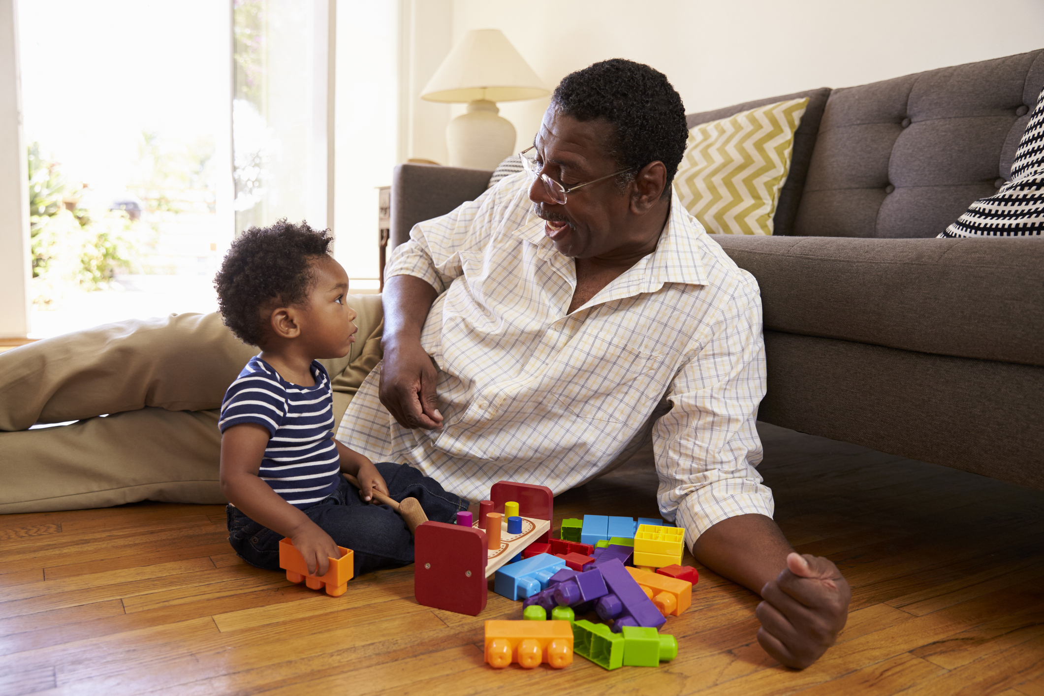 Male caregiver playing on the floor with a sitting baby and some colorful blocks