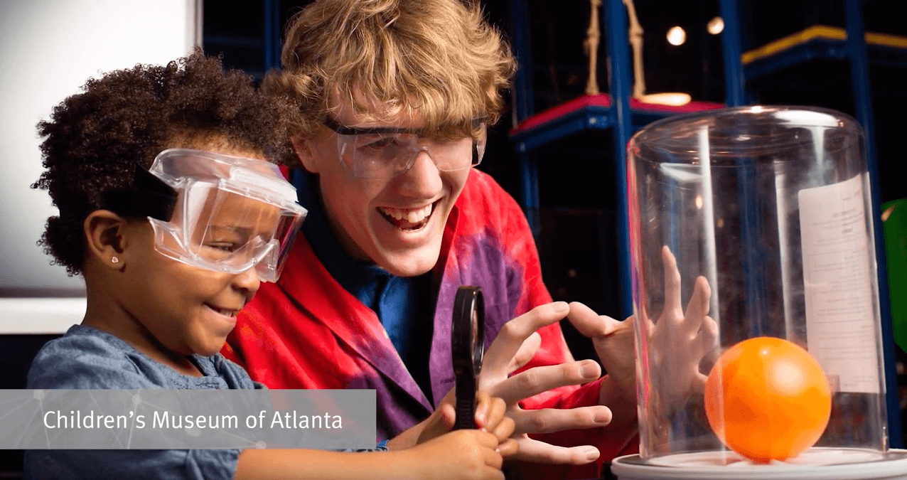 A child and caregiver wearing goggles and doing a science experiment at a children's museum