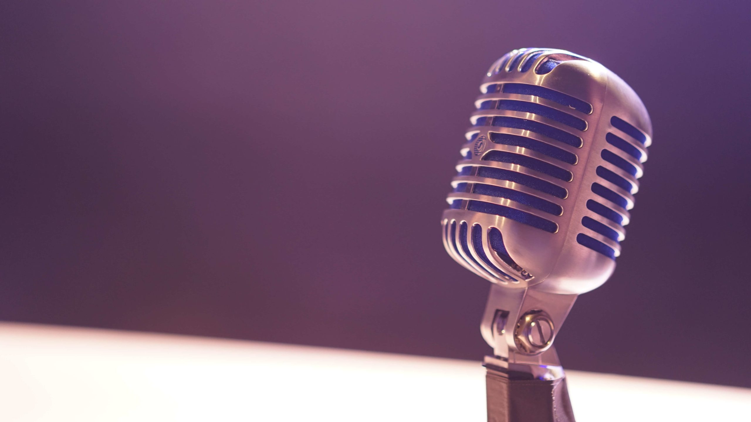 Old-fashioned microphone in front of unfocused black-and-white background Photo by Matt Botsford on Unsplash