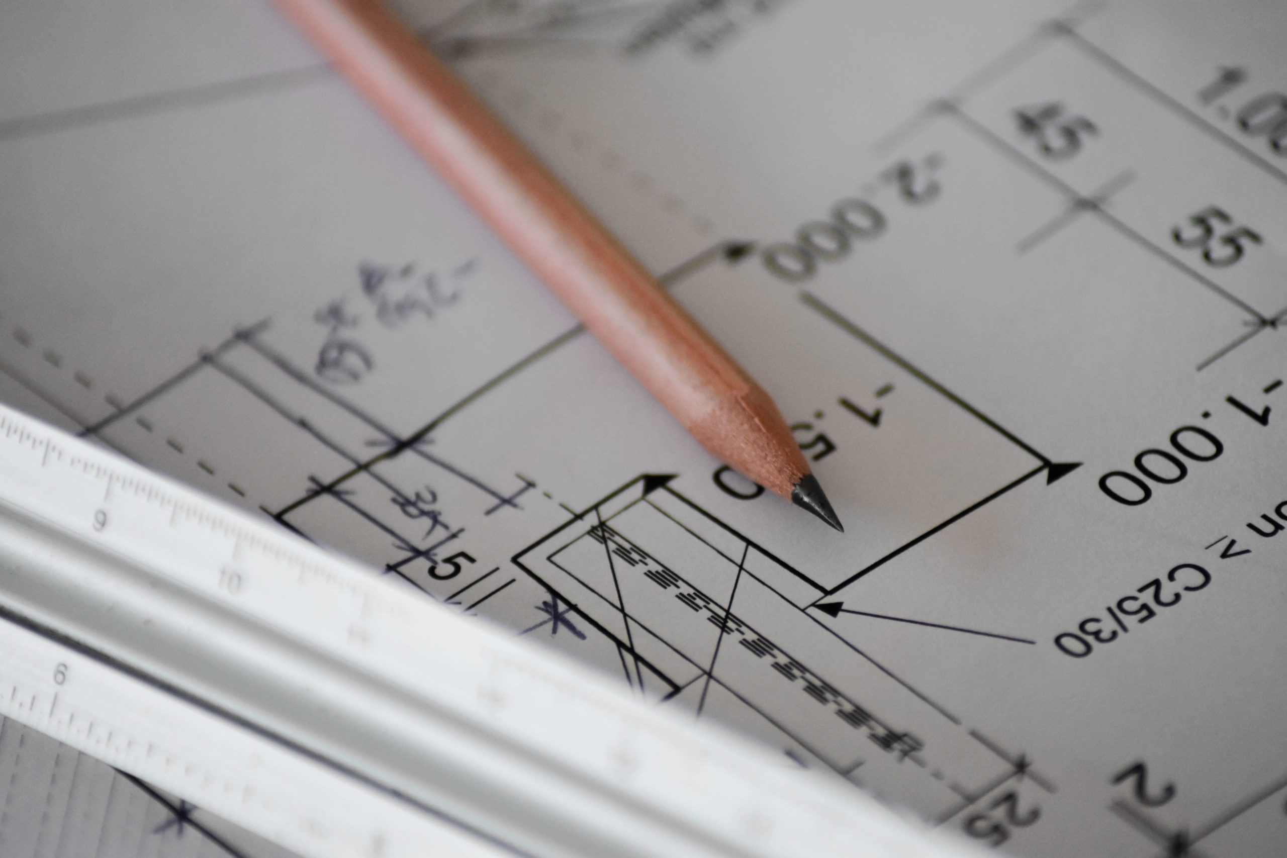Pencil on blueprint with ruler (Photo by Sven Mieke on Unsplash)