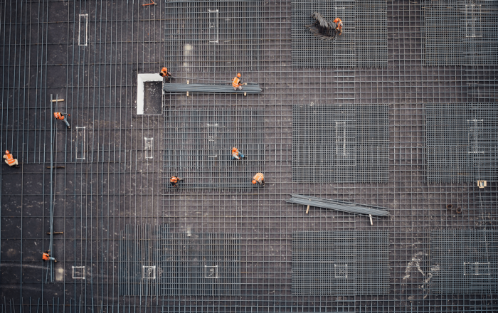 Aerial view of construction workers walking on rebar and building a foundation (Photo by Saad Salim on Unsplash)