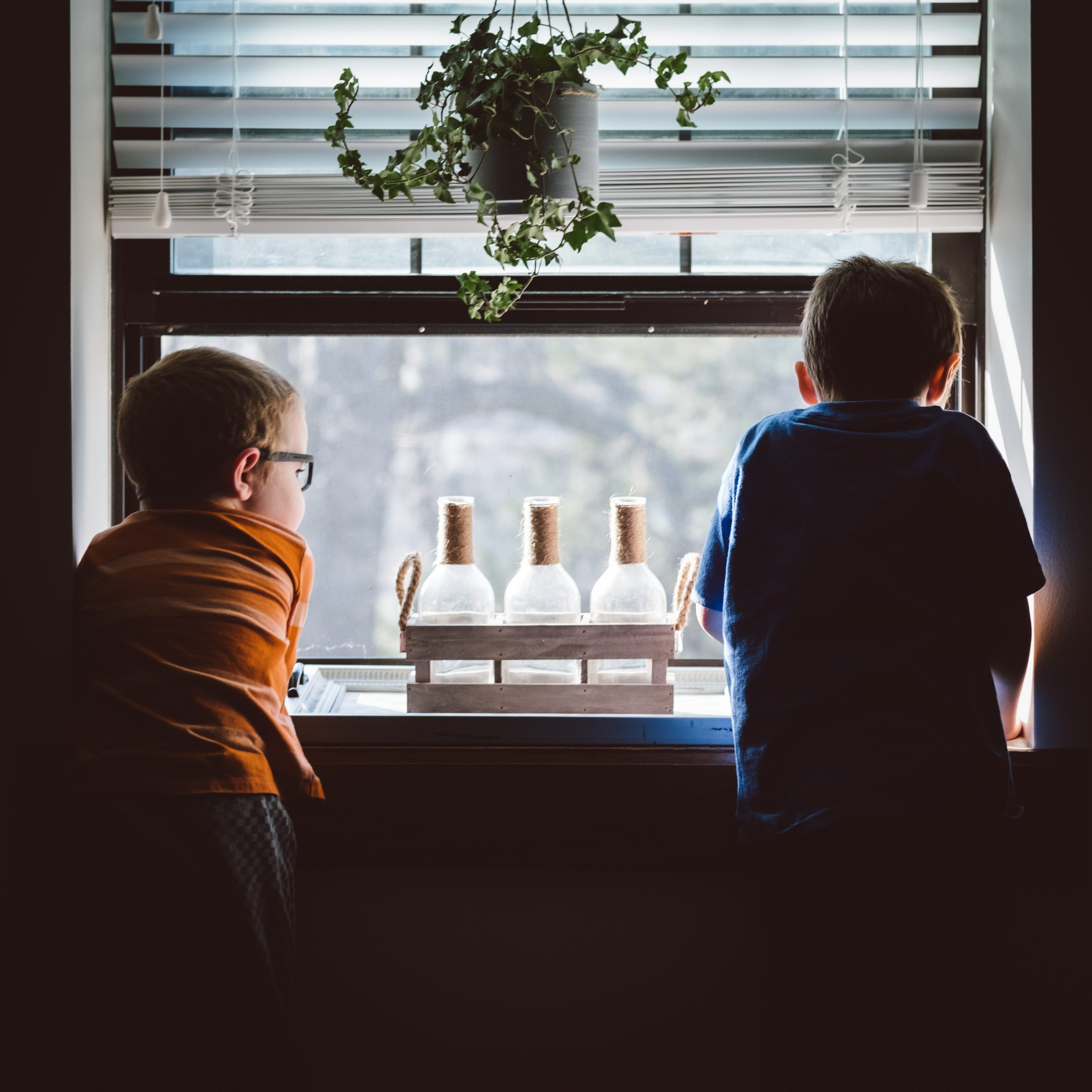 Two boys look out a window (Photo by Andrew Seaman on Unsplash)