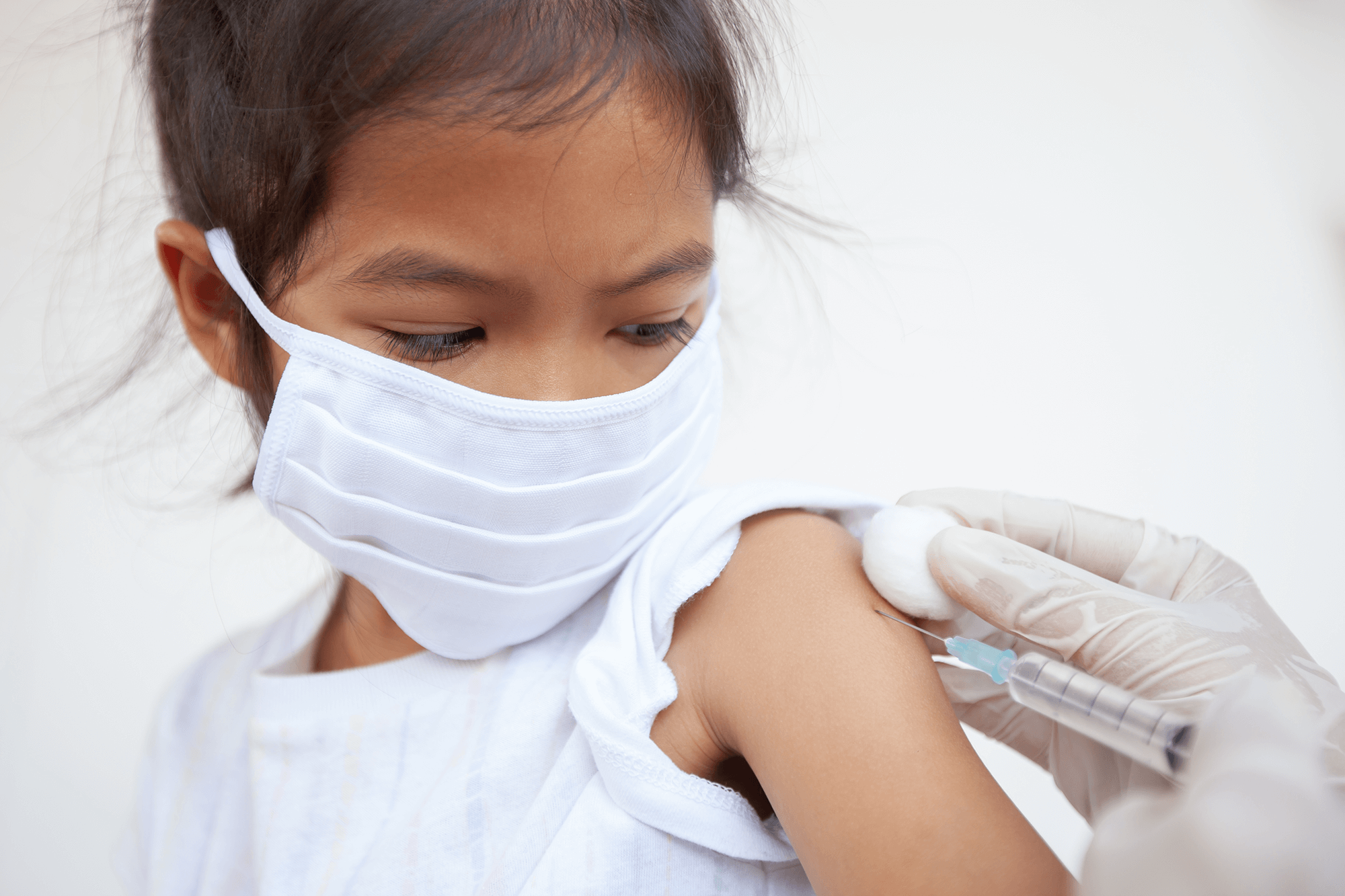 Young girl wearing face mask receives a vaccination