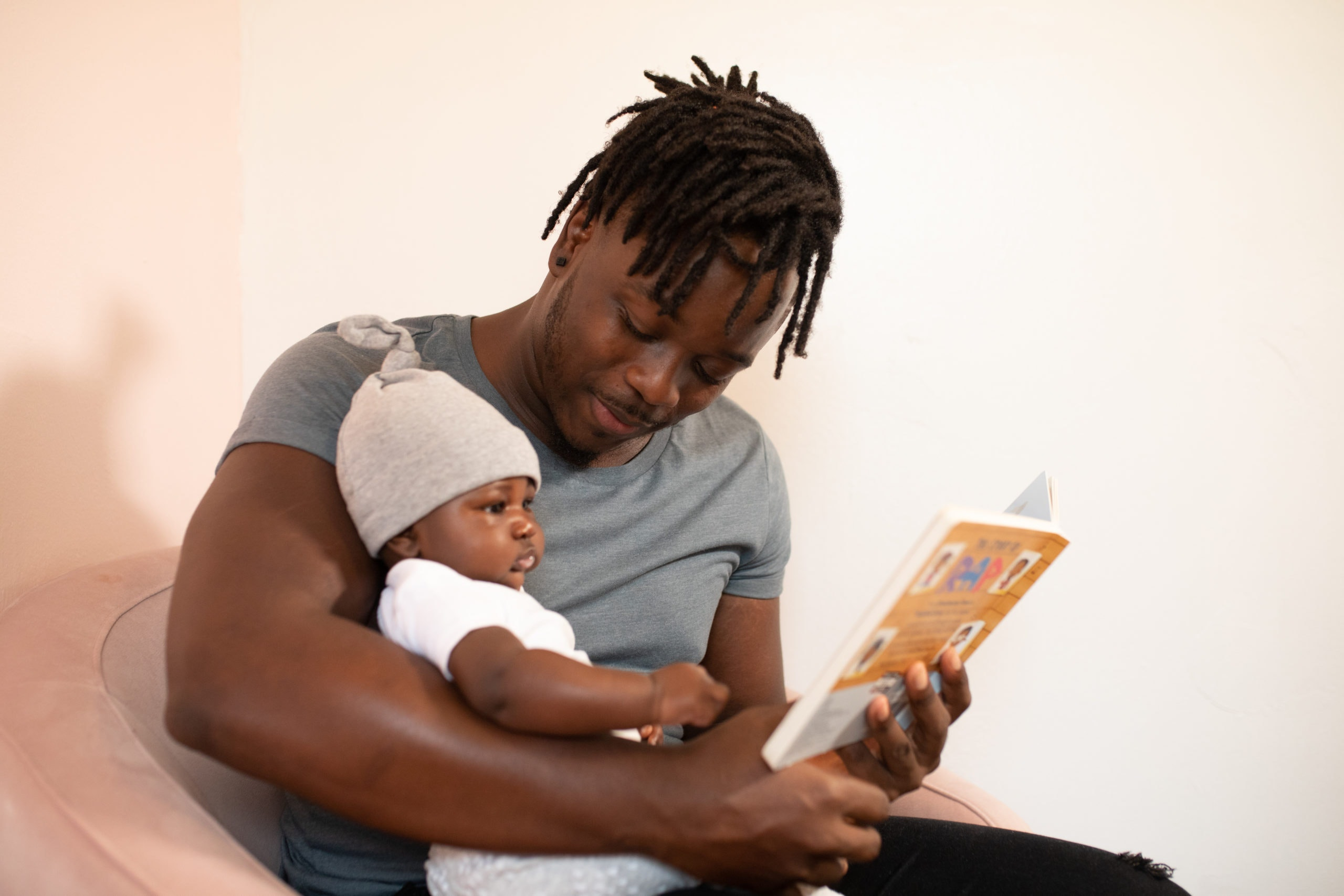 Man sitting in a chair reading to a baby sitting on his lap. (Photo by nappy from Pexels)