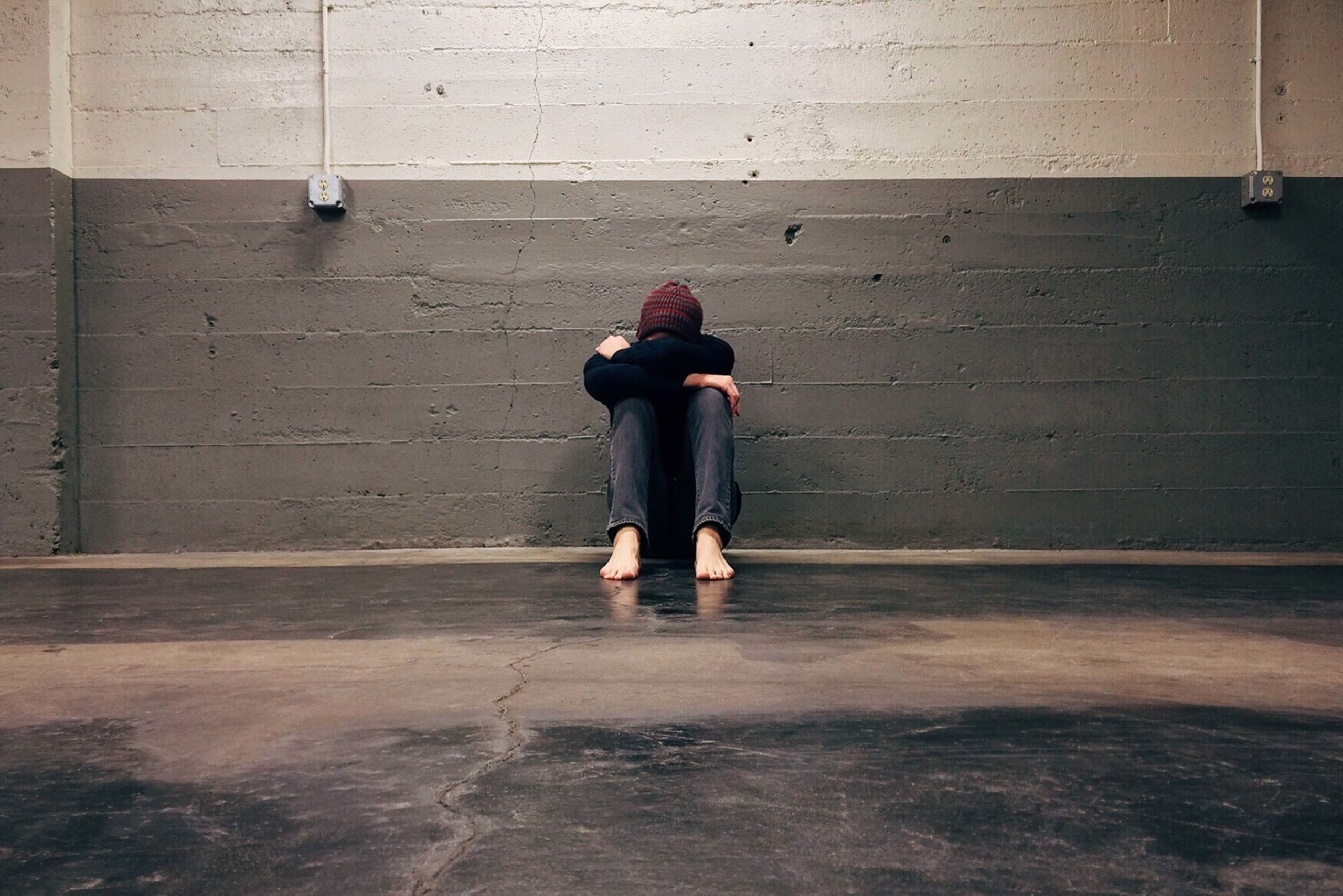 Person sitting with arms crossed and head down leaning up against a wall