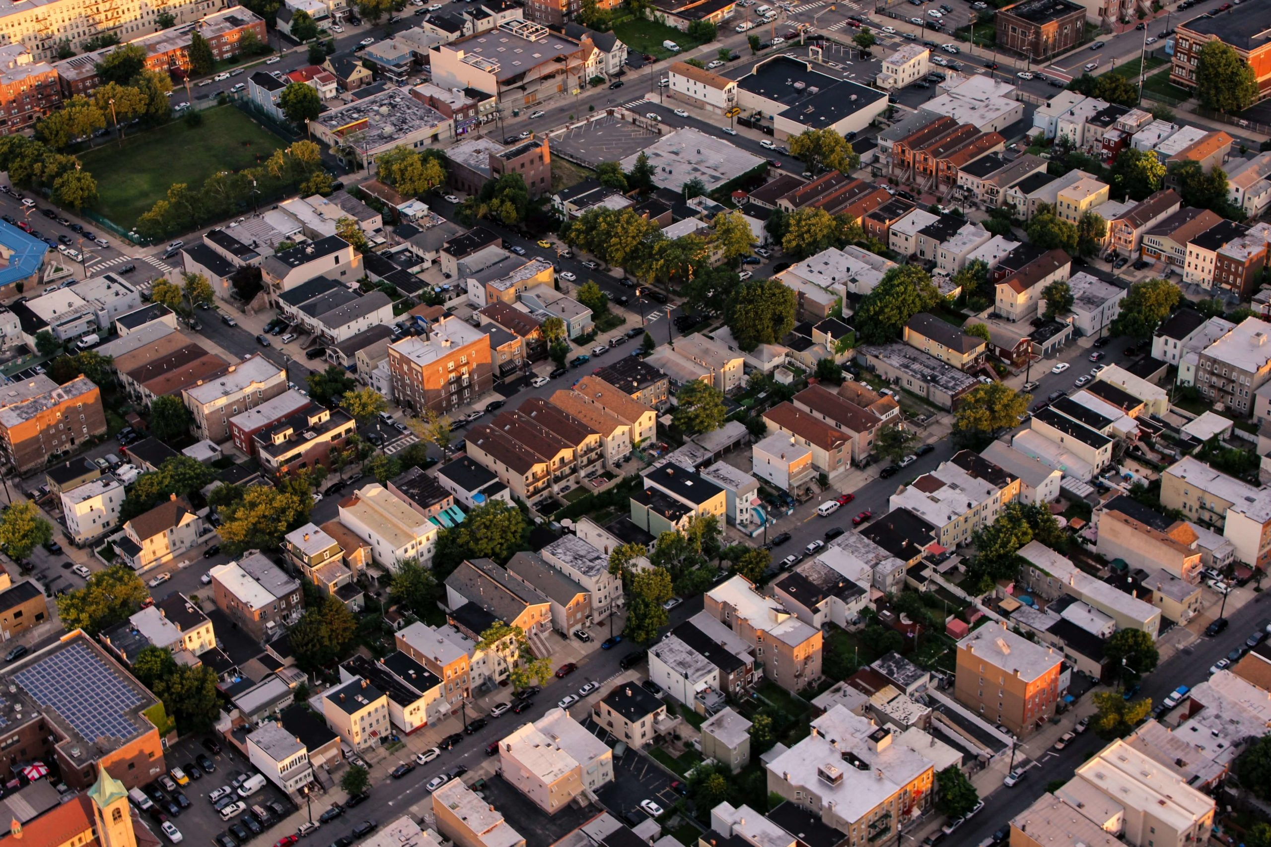Aerial view of a neighborhood with houses, trees, parks, and streets (Photo by Brandon Jacoby on Unsplash)